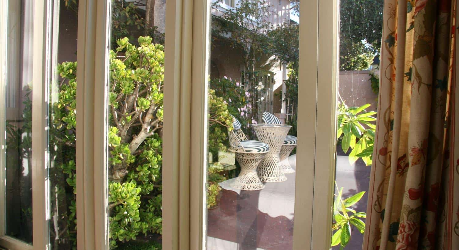 Garden guest room window with view of a courtyard filled with plants, flowers and vines