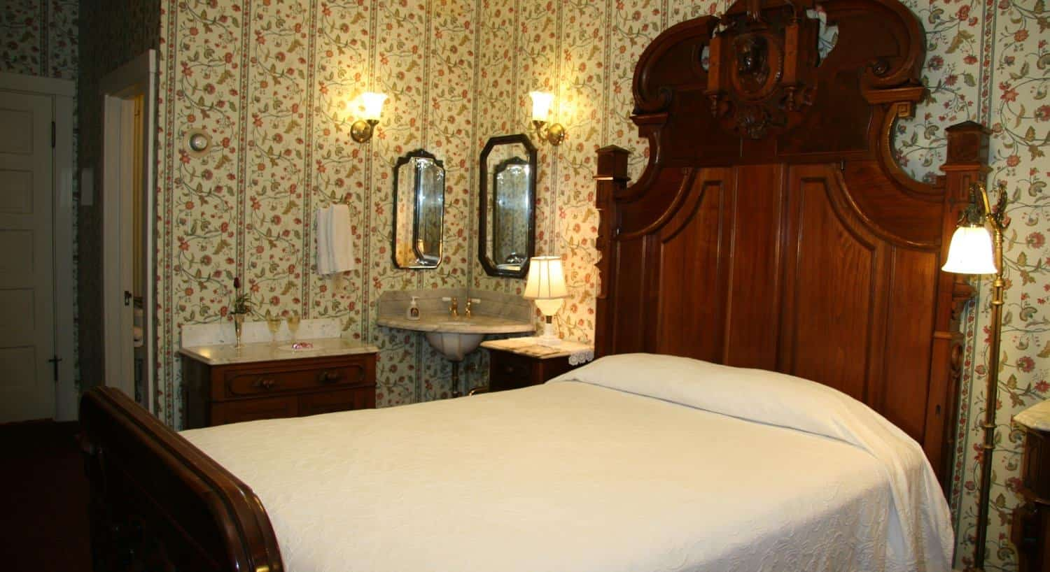 Jenny guest room with floral and striped walls, wood bed, nightstands and wash basin