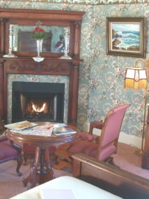 Mahogany guest room with blue floral wallpaper, carpeting, large carved wooden furniture and corner fireplace