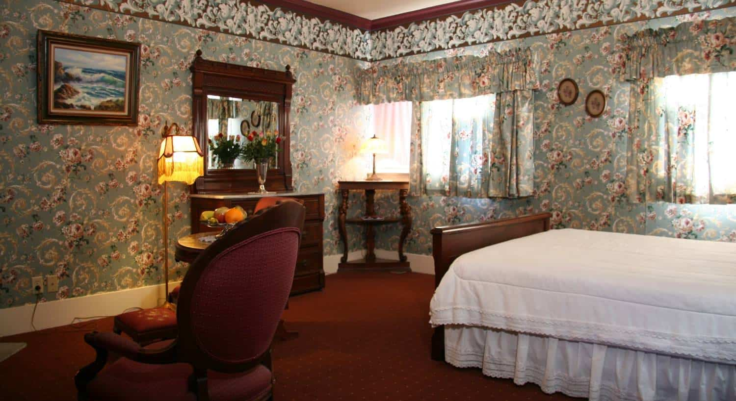 Mahogany guest room with carpeting, blue floral walls, two windows, dresser with mirror and bed with white bedding