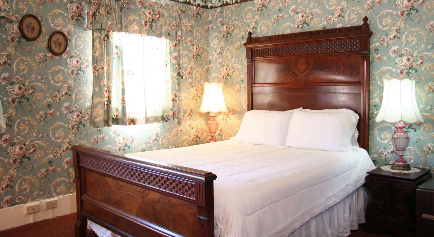 Mahogany guest room with light blue floral walls, window, carved bed with tall headboard, nightstands and lamps