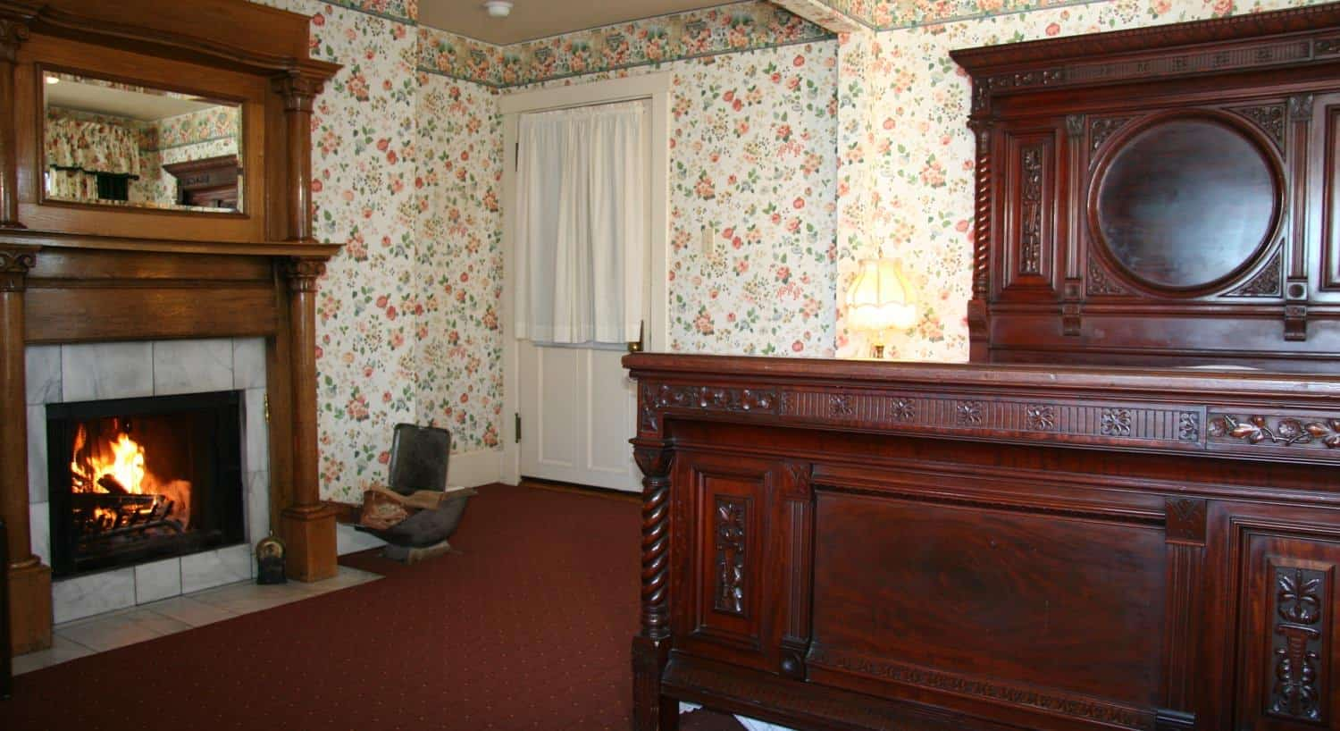 Malarin guest room with floral papered walls, carpeting, fireplace with wood mantel surround, carved wood bed