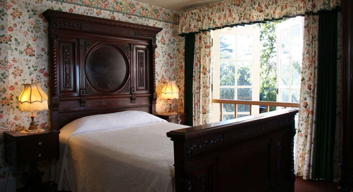 Malarin guest room with floral walls, wood bed with tall carved headboard, two nightstands with fringed lamps and French doors