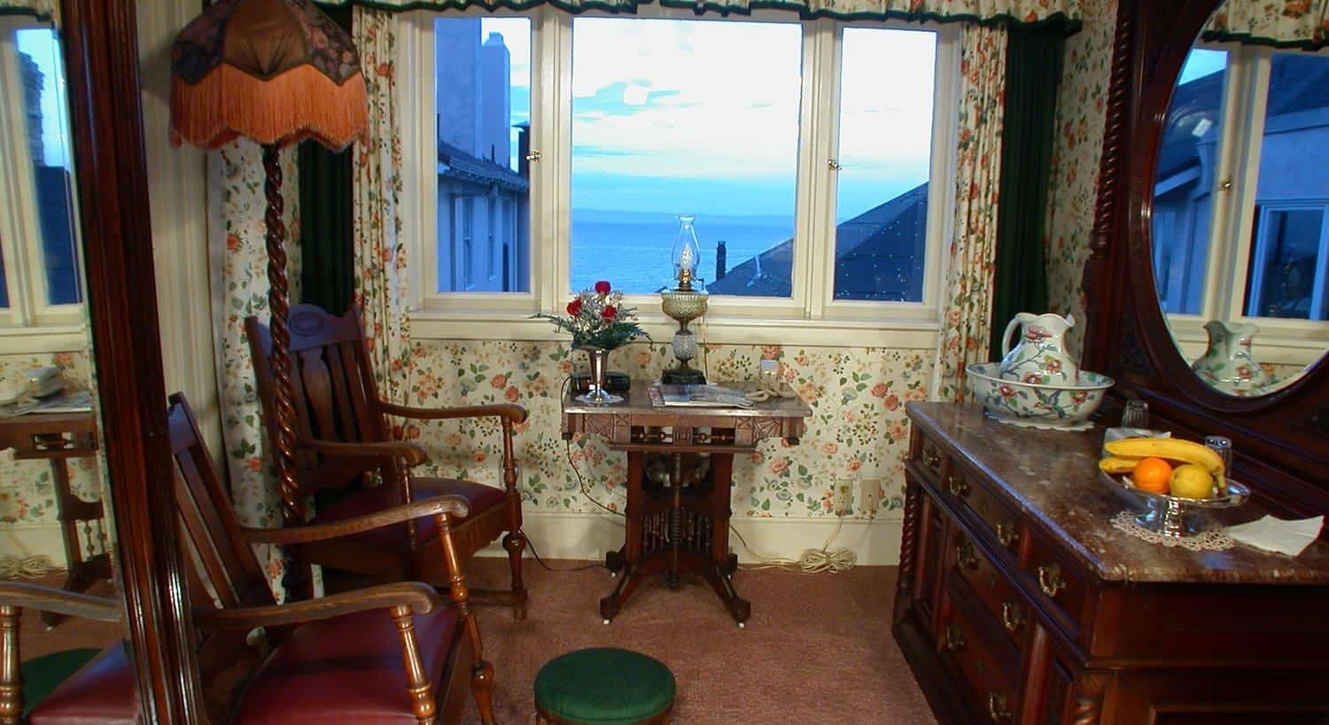 Malarin guest room sitting area with windows, two chairs, small table, dresser with mirror and ocean views