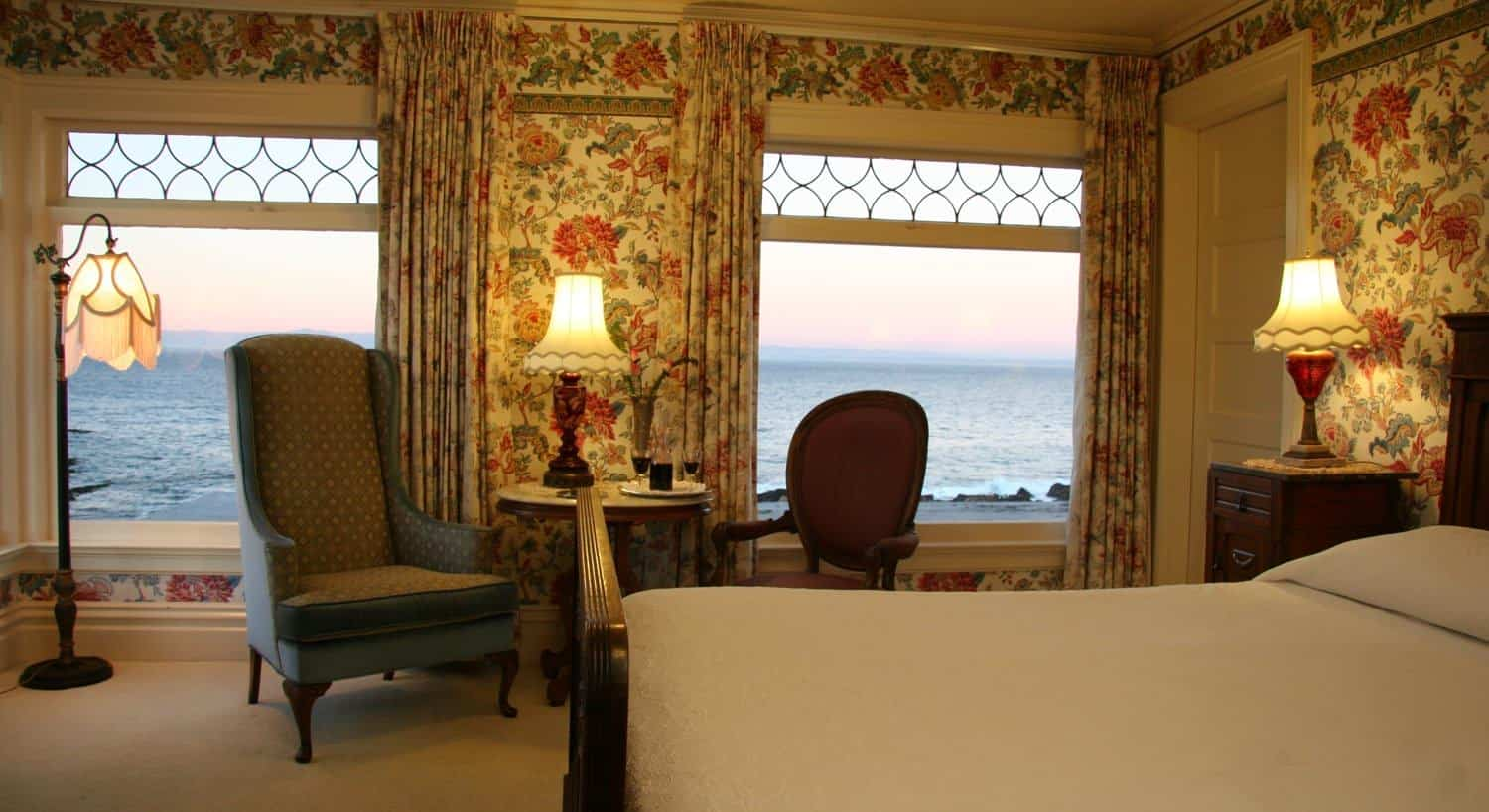 Marie guest room, windows overlooking the ocean, floral papered walls, wood bed and two chairs and a table