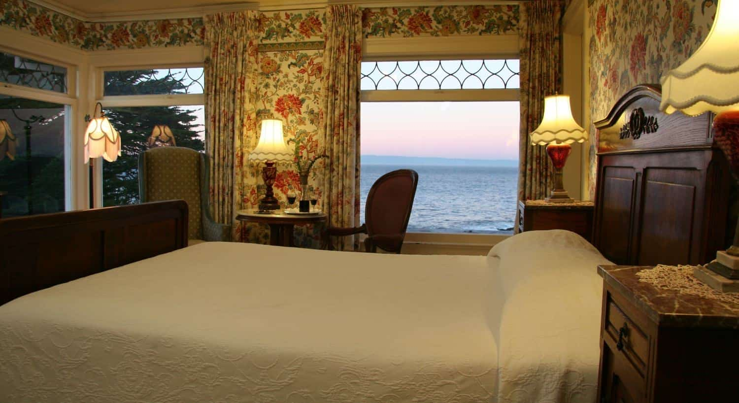 Marie guest room with floral walls, two walls of windows overlooking the ocean, carved wood bed and table with two chairs