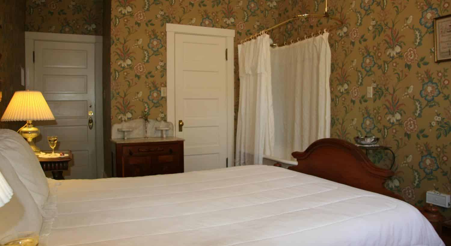 Monterey guest room with gold floral papered walls, wood bed with white bedding, and in-room tub