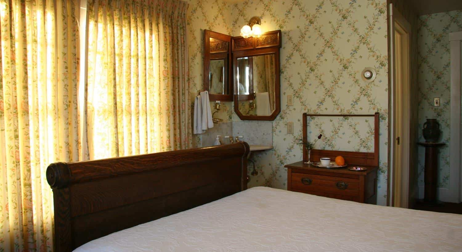 Oak guest room with pastel floral wallpaper, carved bed, corner washbasin and window with floral curtains