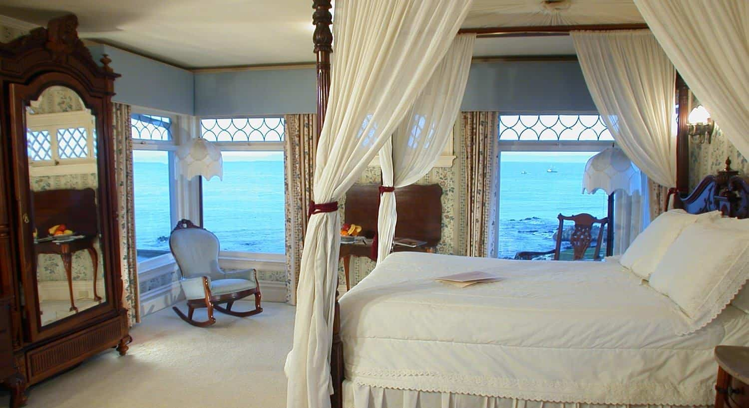 Parke guest room, windows overlooking the ocean, canopy bed with ivory canopy and bedding, sitting chairs and armoire