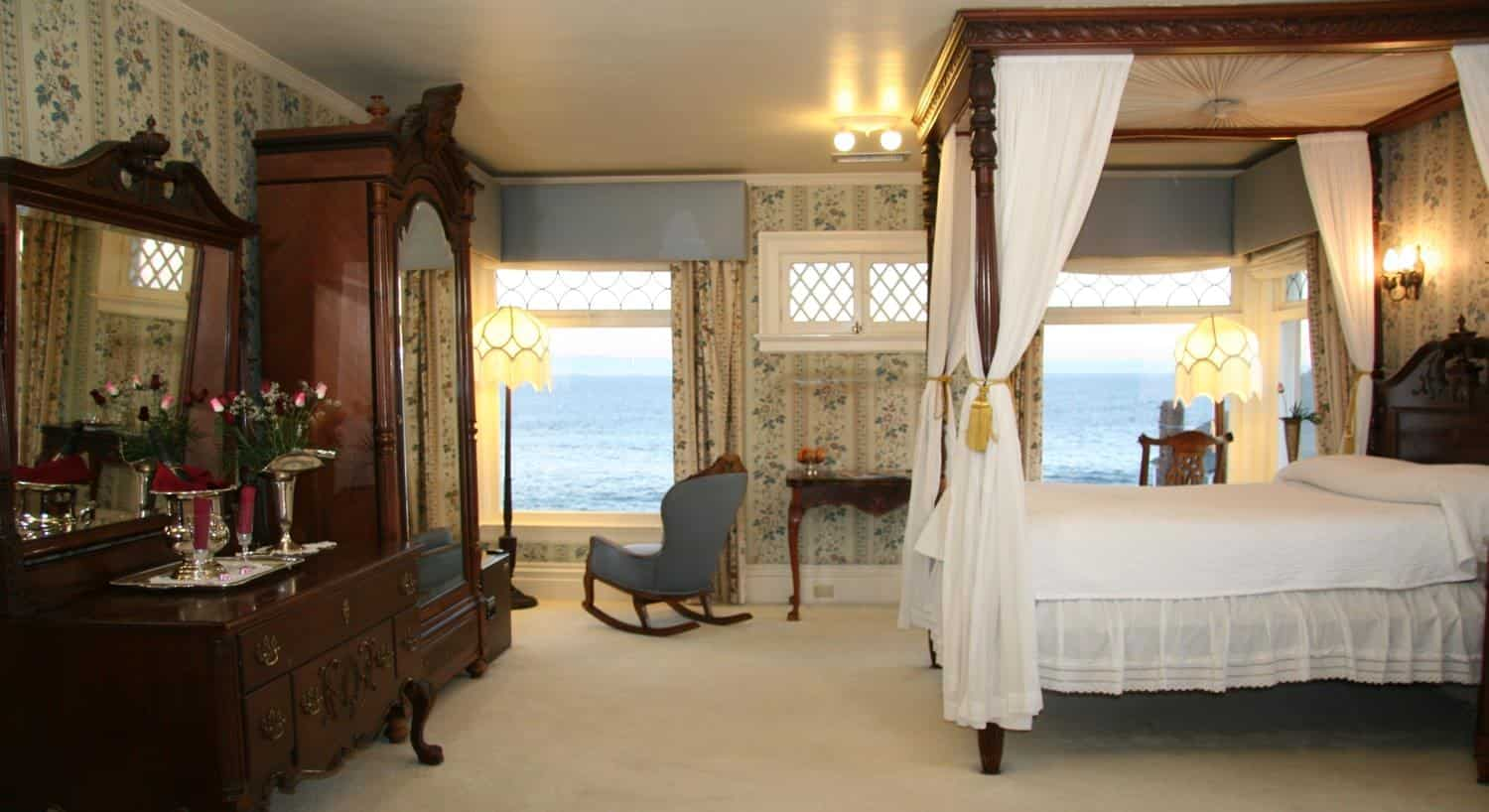 Parke guest room, floral and striped walls, windows overlooking the ocean, canopy bed, mirrored armoire and mirrored dresser