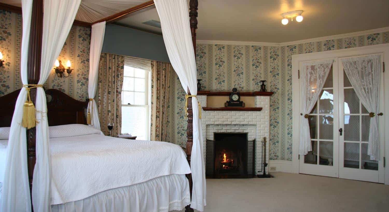 Spacious Parke guest room with carpeting, windows, French doors, corner fireplace and beautiful canopy bed