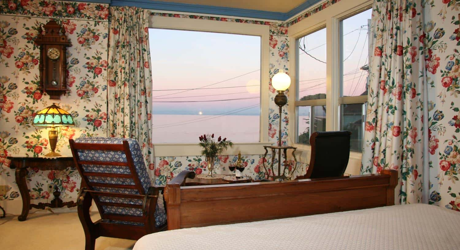 Suite guest room, red and green floral walls, corner windows overlooking the ocean, two sitting chairs and wood bed