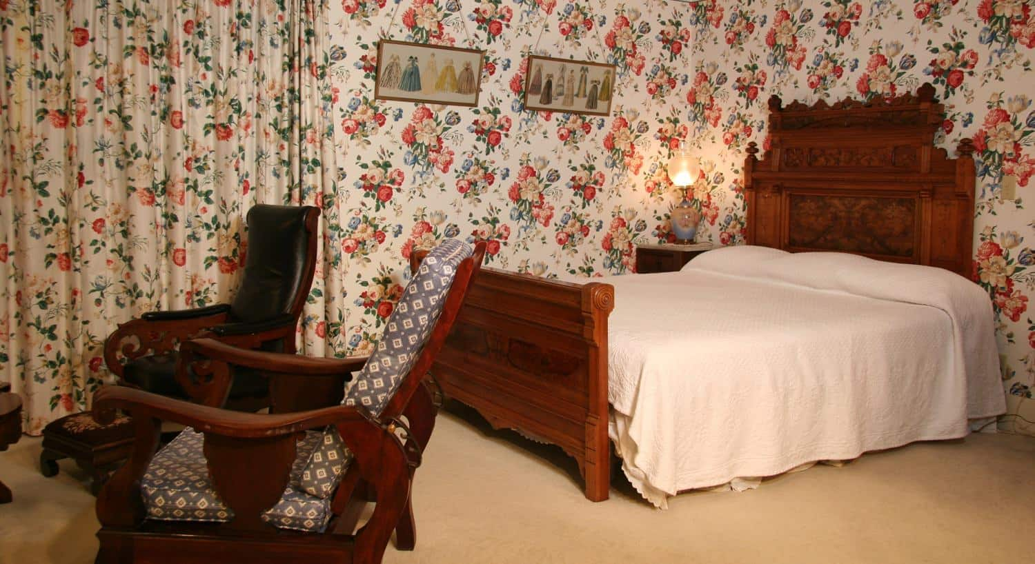 The Suite guest room with red and green floral walls, carpeting, wood bed and two sitting chairs