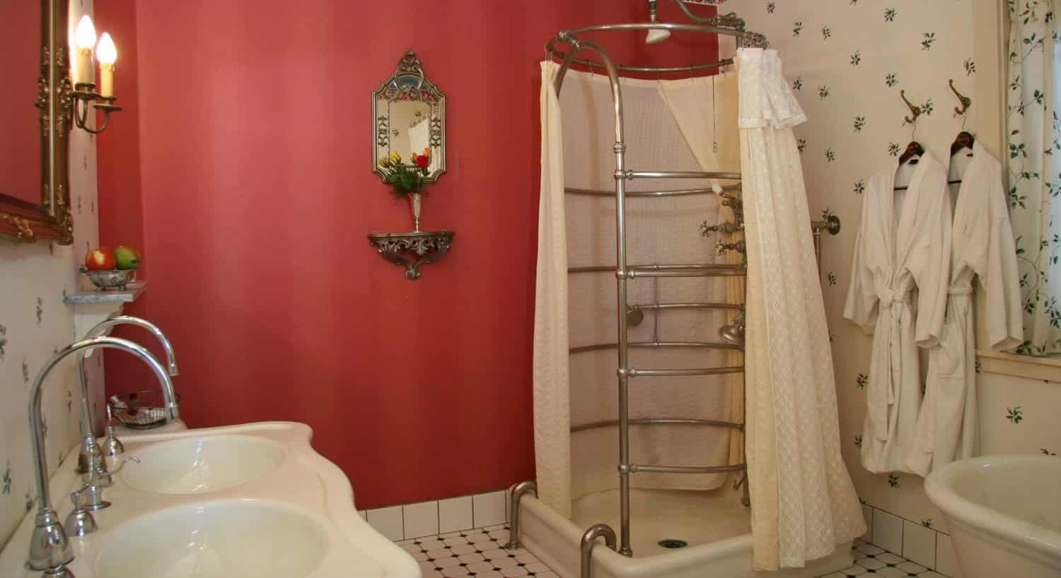 The Suite guest bath with red walls and ivory papered wall, corner shower, freestanding tub and double bowl sink