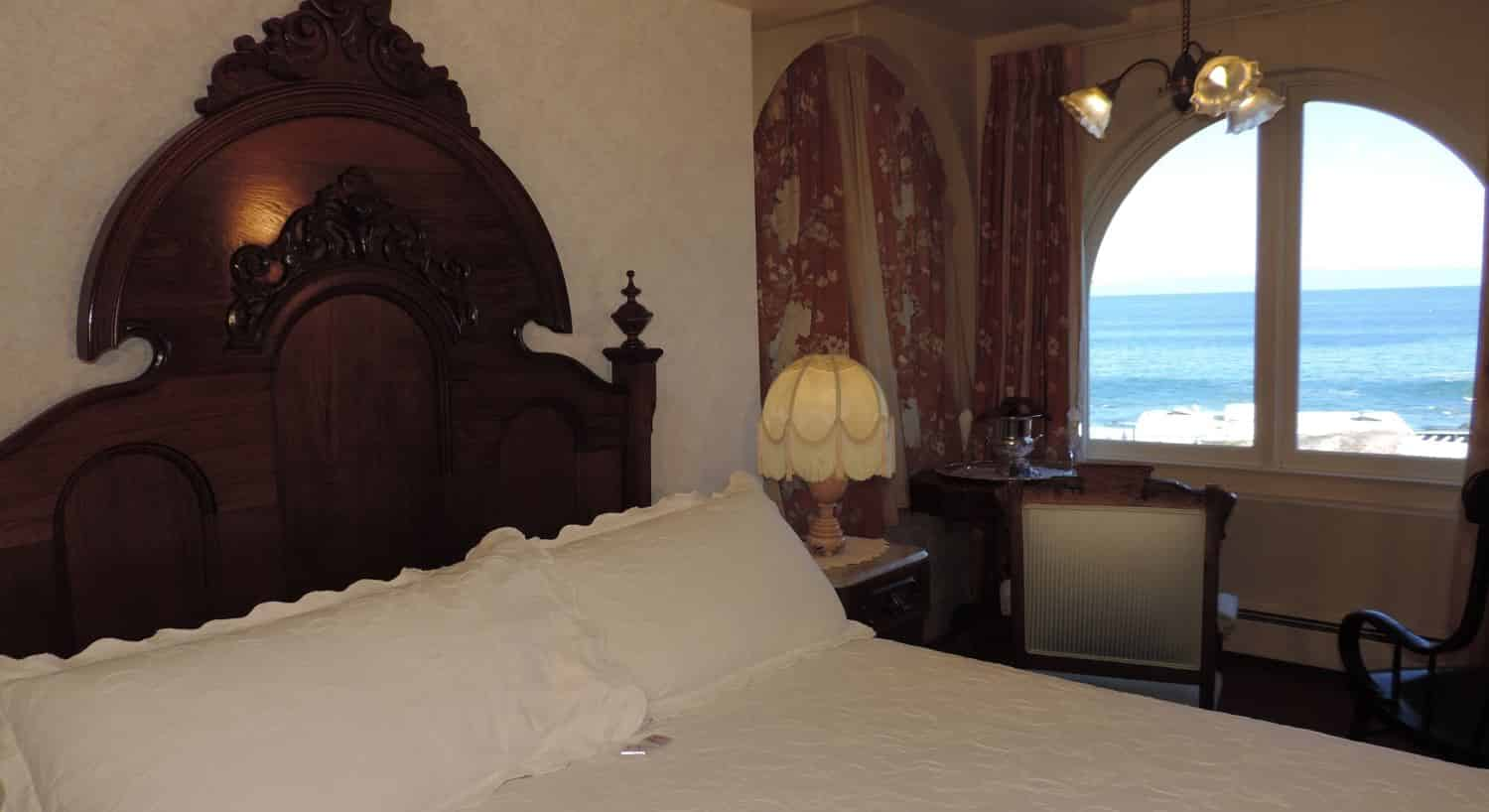 Victoriana guest room with beige walls, arched double window overlooking the ocean and elegantly carved headboard