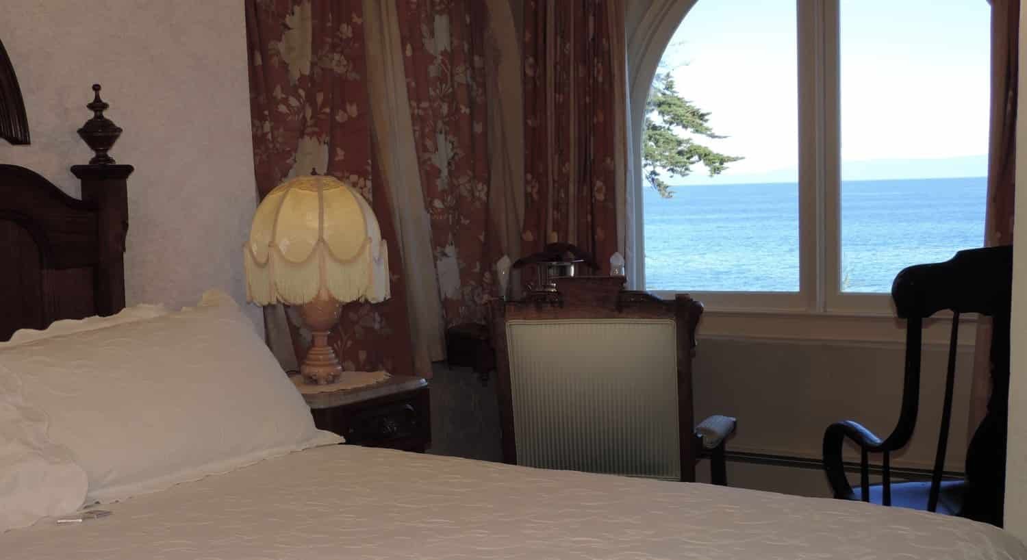 Victoriana guest room with beige papered walls, arched double window overlooking the ocean and carved wooden bed