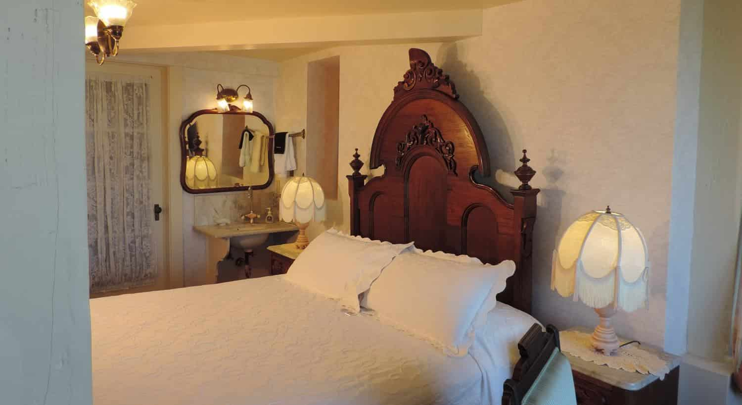 Victoriana guest room with tall carved headboard, white bedding, nightstands with fringed lamps and wash basin with mirror
