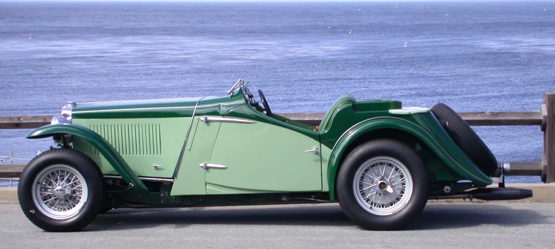 Old classic car in light green and dark green paint parked alongside the Pacific Ocean