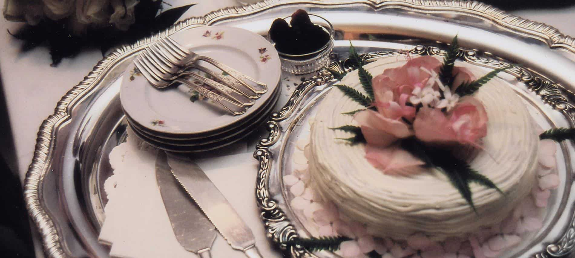 Round silver platter topped with small round white wedding cake with pink flowers and greenery and four plates and forks
