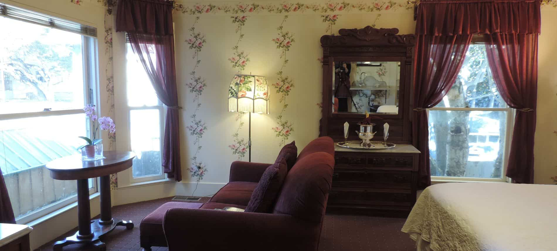 Guest room with ivory floral walls, several windows with curtains, upholstered loveseat and side table with hutch