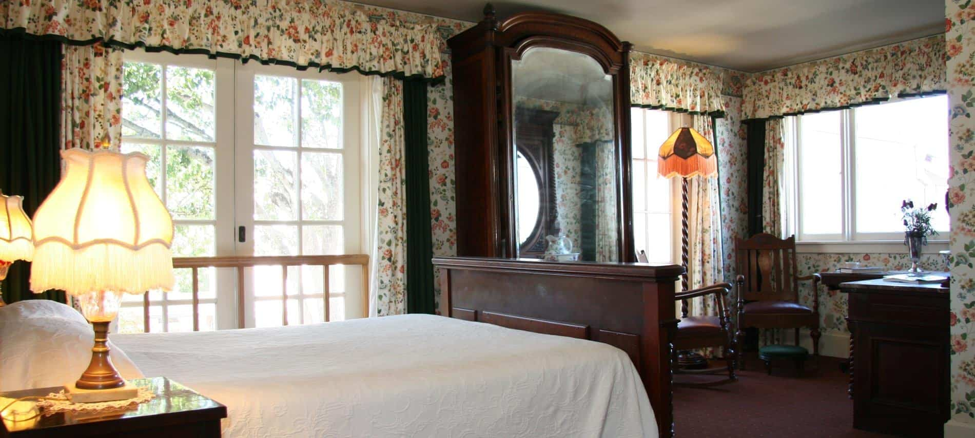 Spacious Fireside guest room with floral papered walls and curtains, several windows, tall armoire with mirror and wood bed