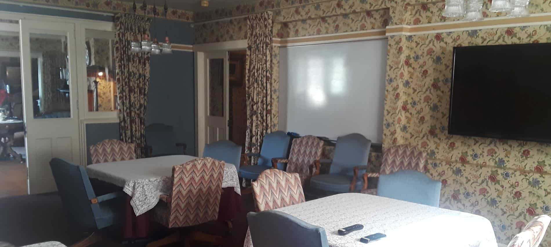 Meeting room with floral papered walls, sliding glass doors, tables for four and extra side chairs