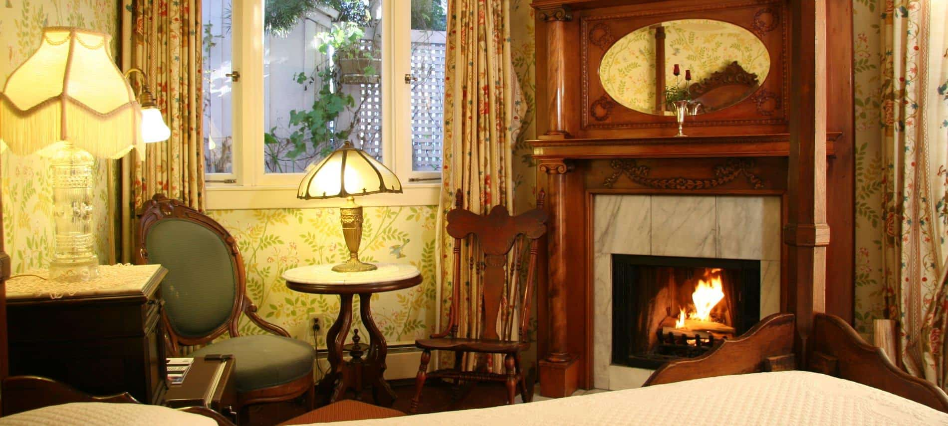 Guest room with papered walls, corner fireplace with warm fire, two chairs and table under a triple window