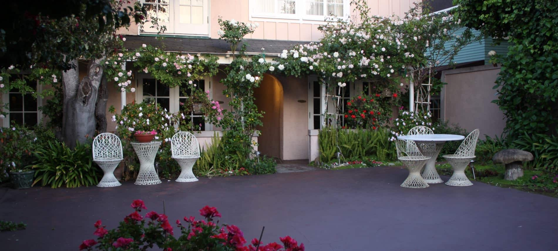 Courtyard surrounded by light pink building, flowering and leafy vines, plants and flowers, and white tables and chairs