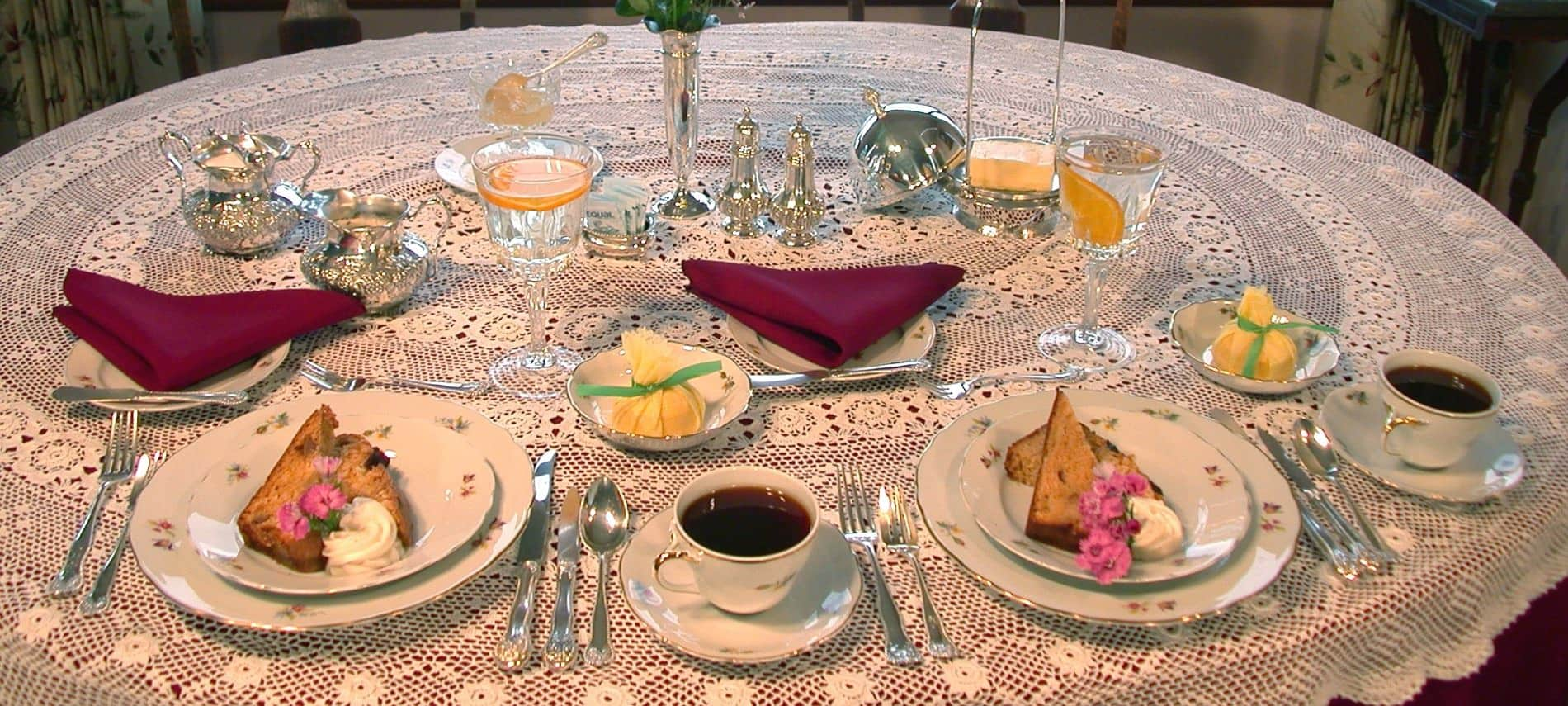 Round table with burgundy cloth and ivory lace topper, white plates with toast and butter, coffee cups with saucers