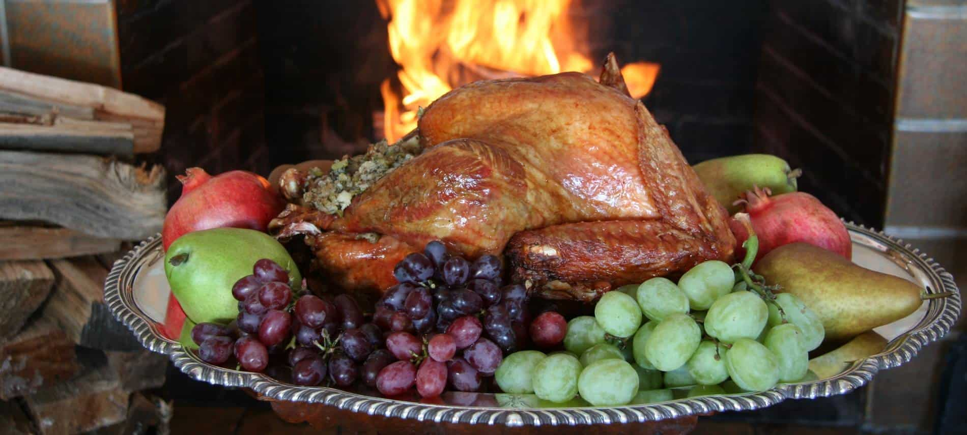 Round silver platter topped with a glistening golden stuffed turkey surrounded by fresh apples, pears and grapes