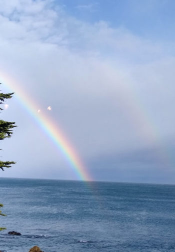 Beautiful large rainbow in a cloudy blue sky over a frothy ocean in Monterey Bay