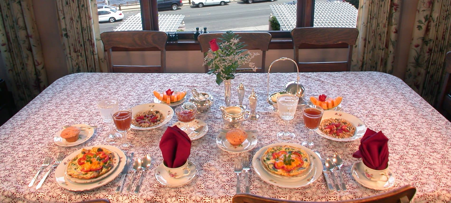 Dining table with white lace topper, set for two with plates of baked quiche, muffins, granola and fruit, juice and water