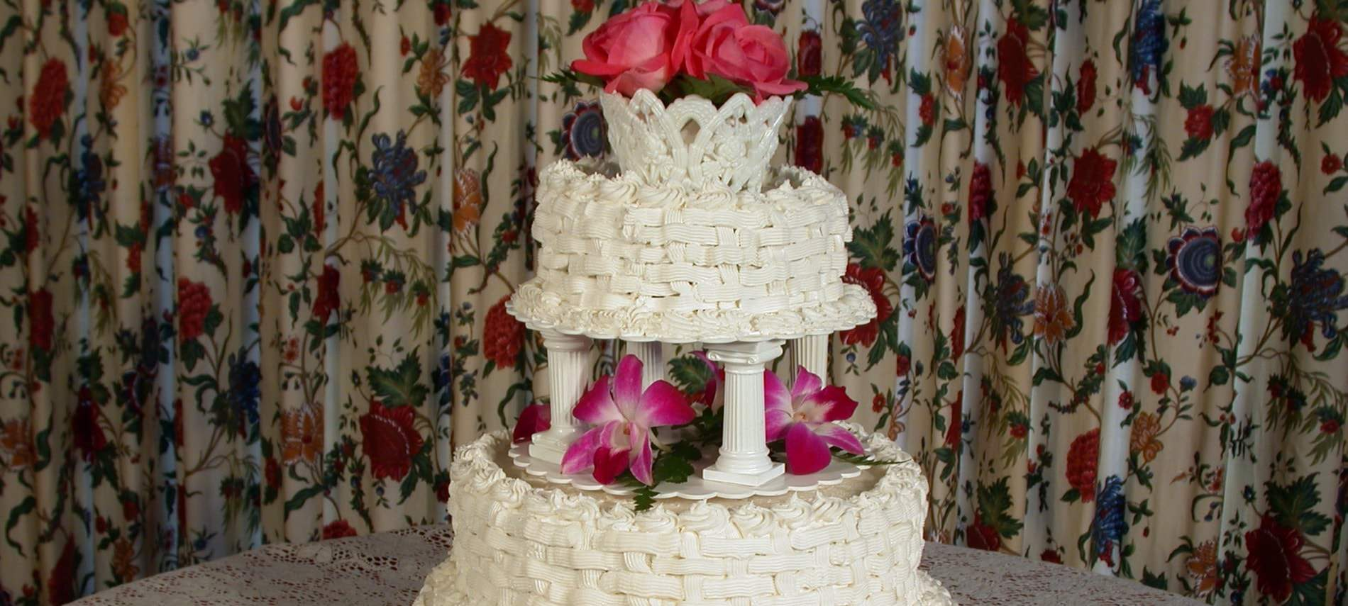 Two tiered ivory wedding cake with basket weave frosting topped with pink and rose flowers