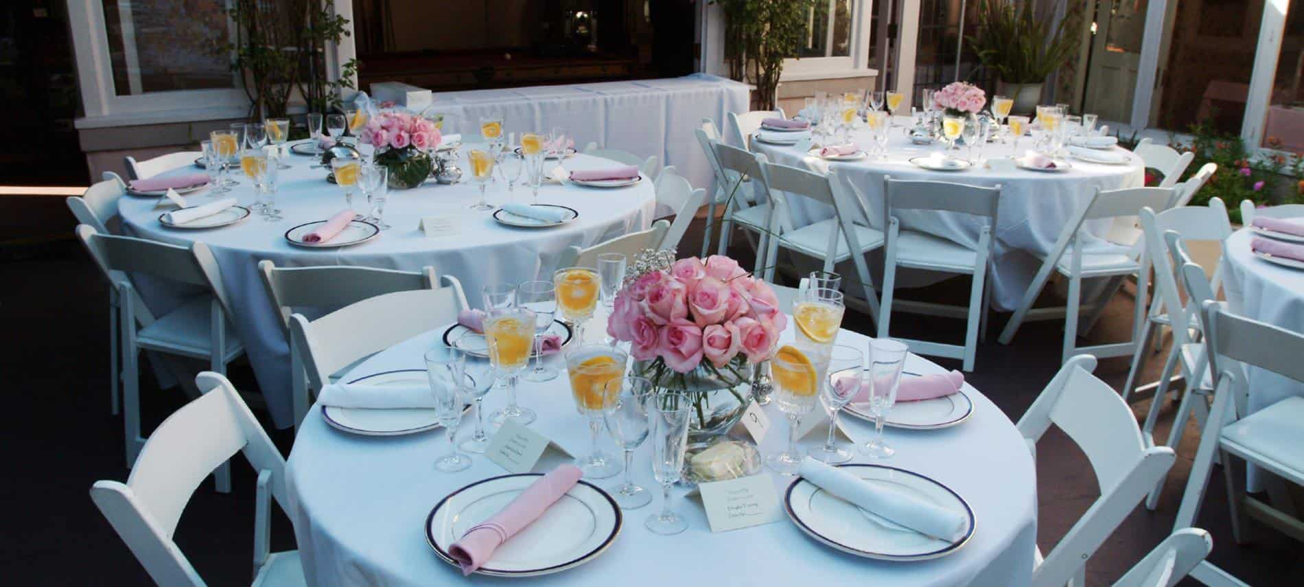 Round white tables and chairs, topped with white cloths and plates, wine glasses, pink napkins and vases of pink roses