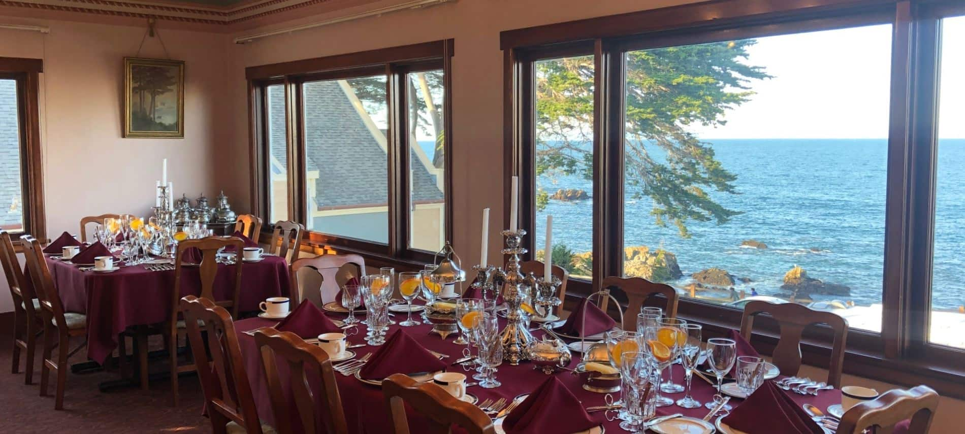 Tables set with burgundy cloths and napkins, water glasses with fresh orange slices, assorted wine glasses, overlooking Monterey Bay