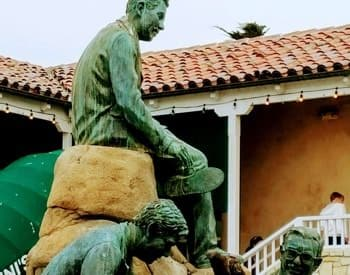 Steinbeck Monument: Patina statue of several men next to a building with red tile roof