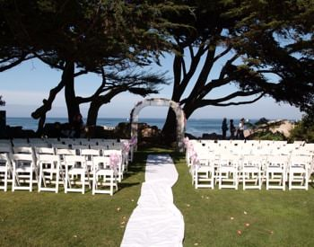 Wedding set up under trees overlooking the ocean, white aisle runner leading to arched trellis flanked by rows of white chairs