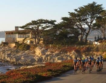 Group of cyclists riding down a road along the Monterey Bay shoreline