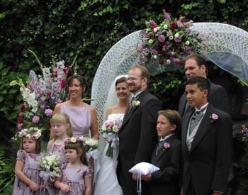 Bride and groom flanked by maid of honor, groomsman, ring bearers and flower girls next to a white arched trellis