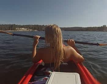 Backside of a woman with long blonde wet hair holding an oar in a red kayak surrounded by water
