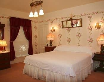 Guests room with ivory floral papered walls, white covered bed, two nightstands, window with curtains
