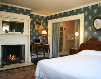 Guest room with white covered bed, blue floral papered walls, fireplace, and desk with chair
