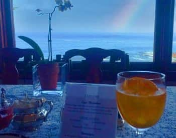 View of a rainbow outside the dining room with a cold beverage in a wine glass on the table