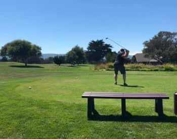 Grassy green golf course with man in the middle of a swing amidst bright blue skies
