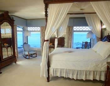 Guest room with several windows overlooking the ocean and four poster canopy bed with white canopy and bedding