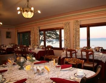 Parlor with wall of windows overlooking Monterey Bay, and several lace topped dining tables set for a meal