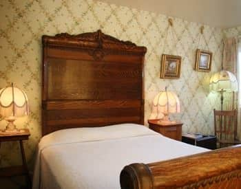 Guest room with bed, tall headboard, two nightstands, papered walls and antique lamps