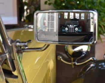 View of an antique car through the side mirror of another yellow antique car