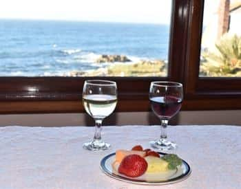 Two wine glasses on a table next to a plate of fresh fruit overlooking the Bay