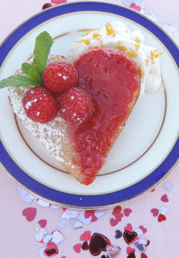 A slice of fruit tart cut into a heart shape on a chine plate with a blue and gold rim.